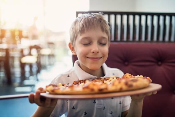 在餐館嗅到比薩的小男孩 - 即食口糧 個照片及圖片檔