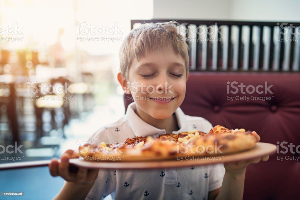 Kleiner Junge riechen Pizza im restaurant – Foto