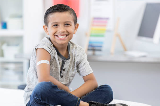Little boy smiles proudly at camera after vaccination An adorable little elementary age boy sits cross legged on an exam table in his pediatrician's office.  He displays an arm bandage as he smiles for the camera. adhesive bandage stock pictures, royalty-free photos & images