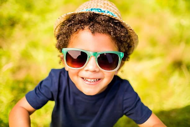kleine junge lächelnd in die kamera im park - sonnenbrille kleinkind stock-fotos und bilder