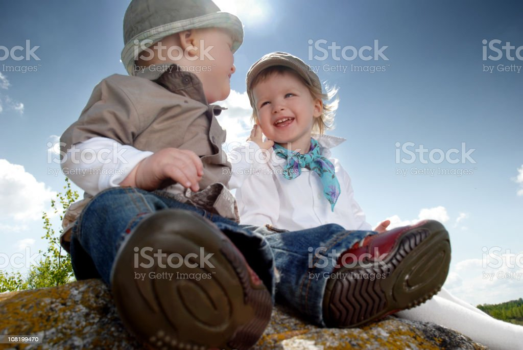 Little Boy Smiling at His Sister and Sitting on Rock royalty-free stock photo