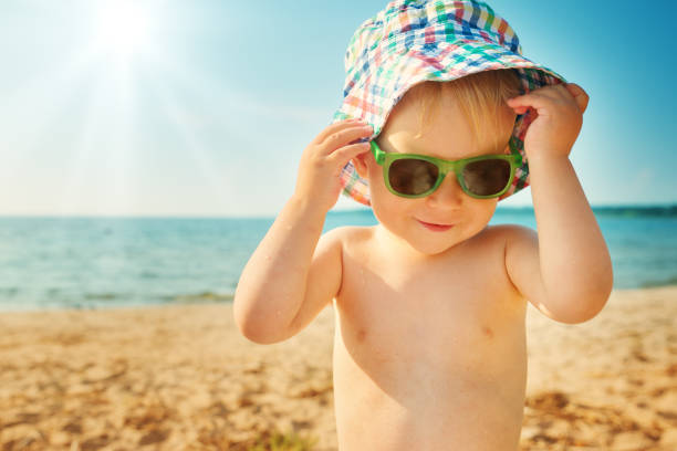 kleiner junge am strand im hut mit sonnenbrille lächelnd - sonnenbrille kleinkind stock-fotos und bilder