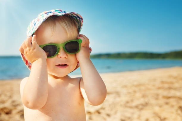 little boy smiling at the beach in hat with sunglasses stock photo