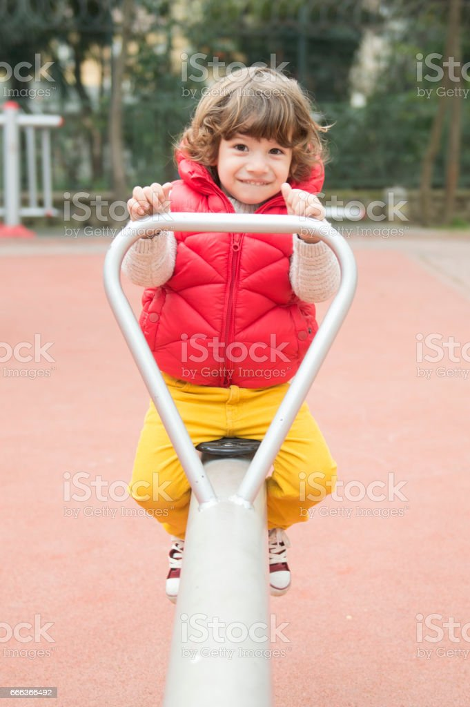 Little boy smiling on a playground teeter totter stock photo