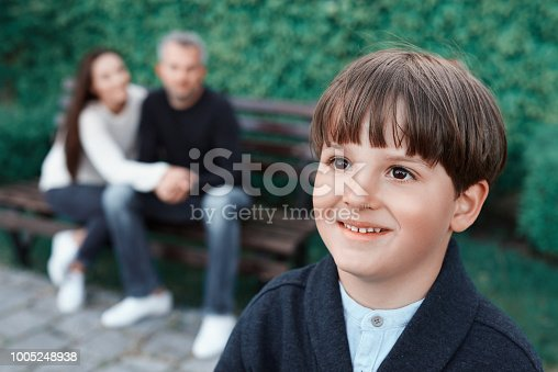 cute little boy with toothy smile looking away in park, parent on bench behind him.