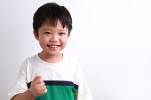 Portrait of little Asian boy smiling, rejoicing, clenching fist, isolated on white