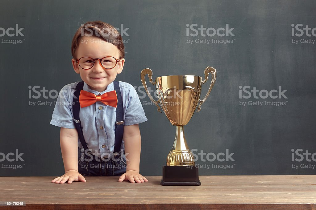 Little boy smiling with a golden trophy stock photo