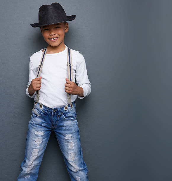 Little boy smiling with black hat and suspenders Portrait of a little boy smiling with black hat and suspenders on gray background suspenders stock pictures, royalty-free photos & images