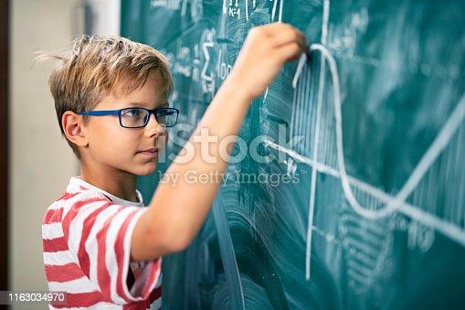 istock Little boy solving advanced mathematical problems 1163034970