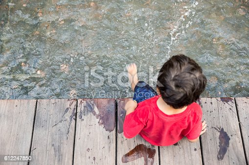 istock Little boy splashing water 612247850