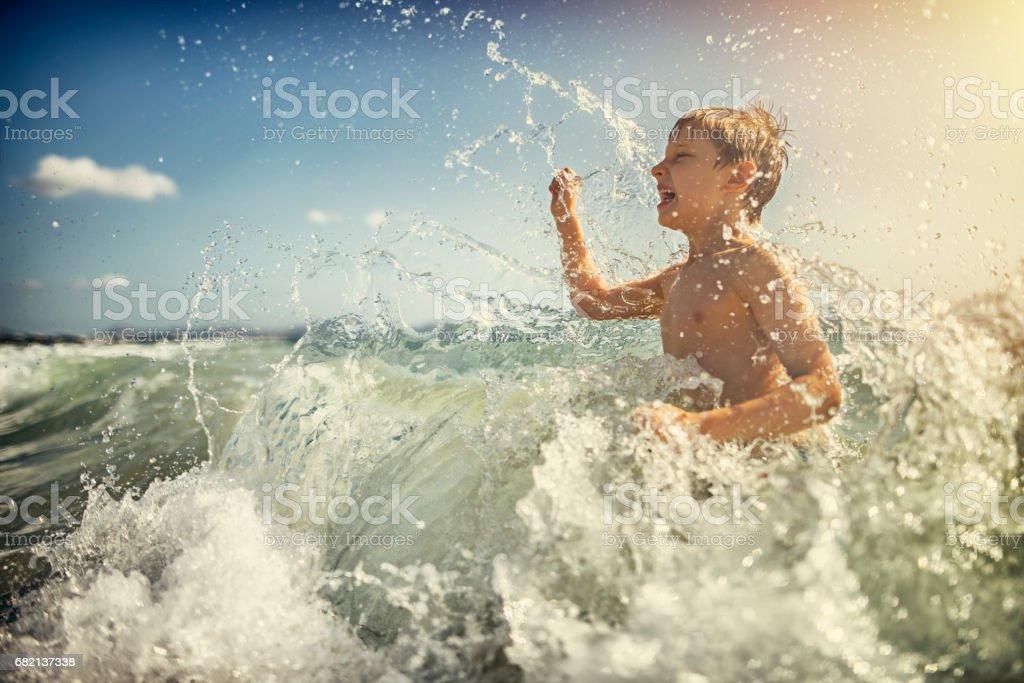 Little boy splasing in the sea waves stock photo