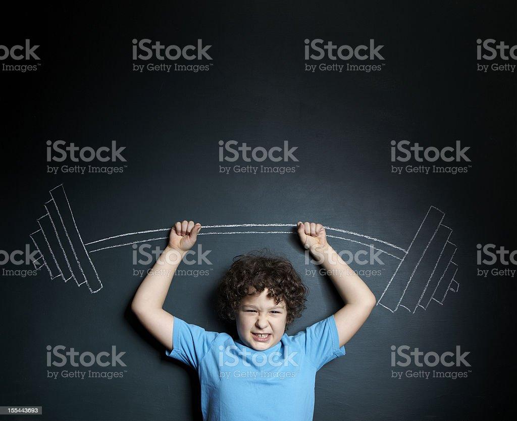 A little boy standing against a blackboard stock photo