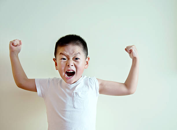 Little boy standing against wall showing his muscles Little boy standing against wall showing his muscles. flexing muscles stock pictures, royalty-free photos & images