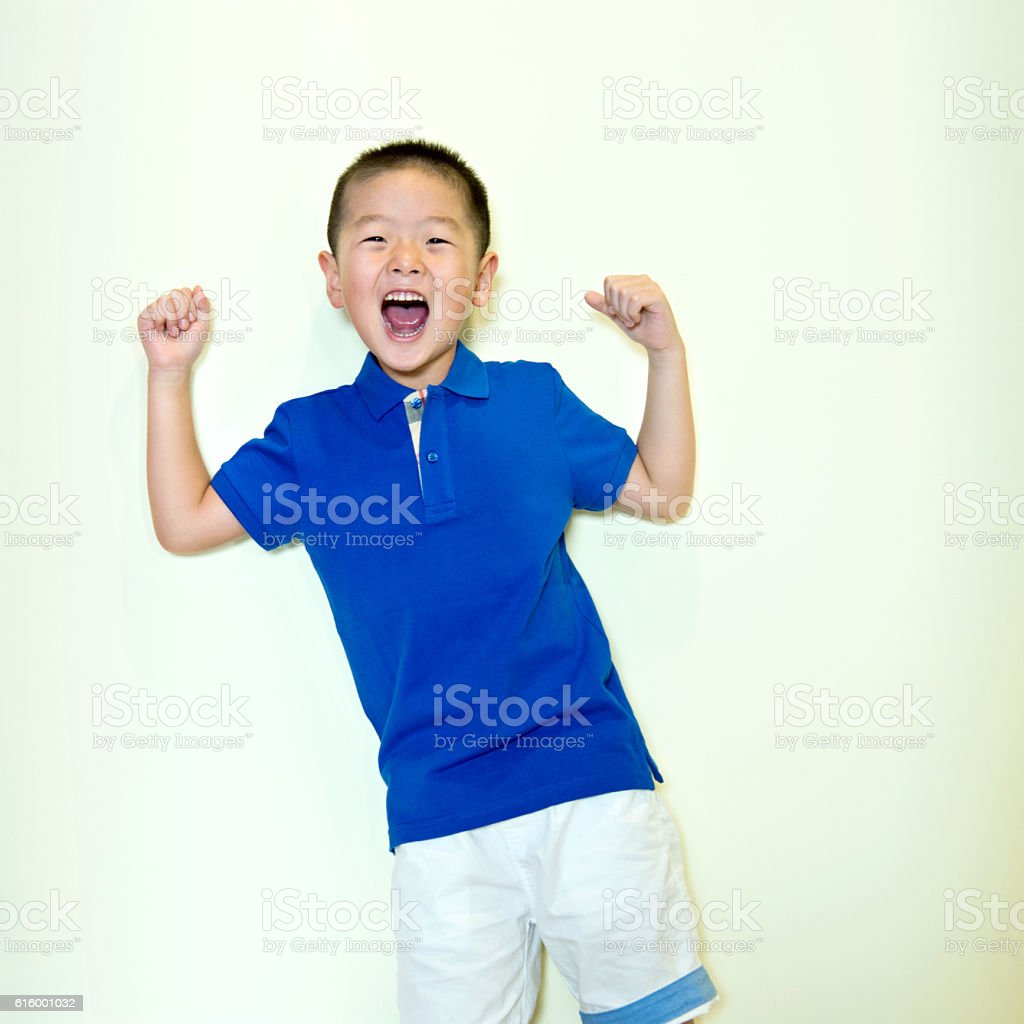 Little boy standing against wall showing his muscles stock photo