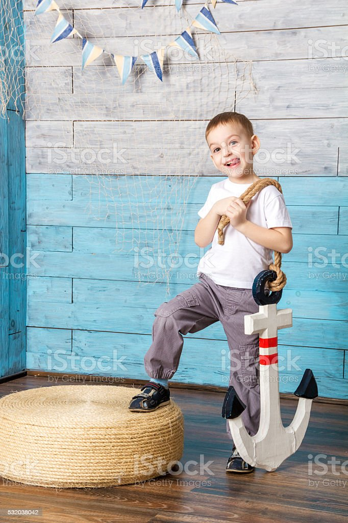 little boy standing and holding an anchor stock photo