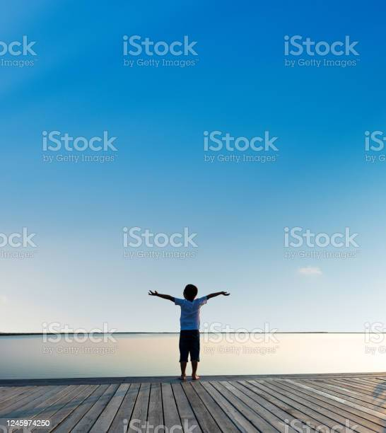 Photo of Little boy standing at lakeside with arms outstretched