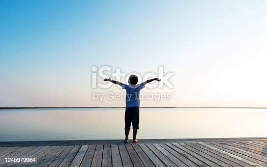 Little boy standing at lakeside with arms outstretched.