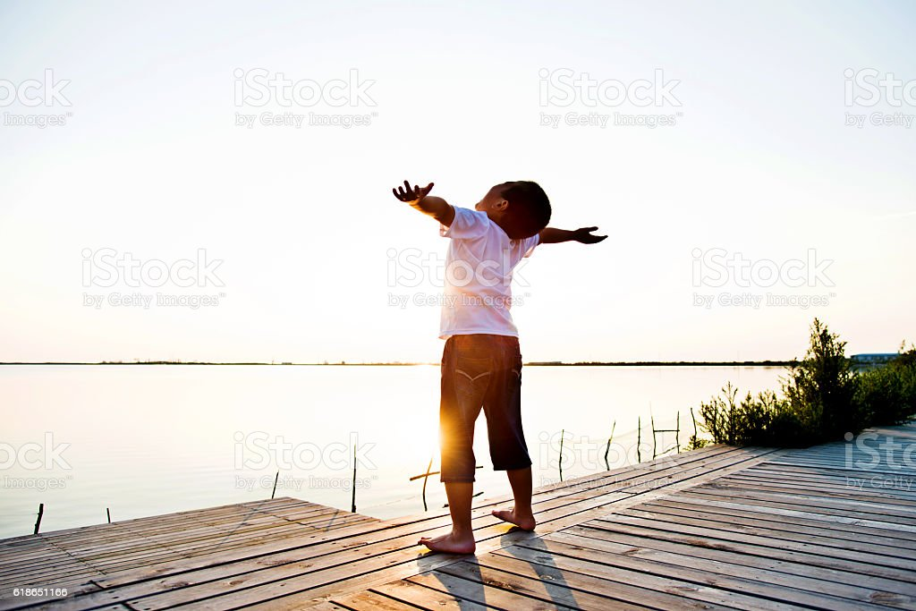 Little boy standing at lakeside with arms outstretched stock photo