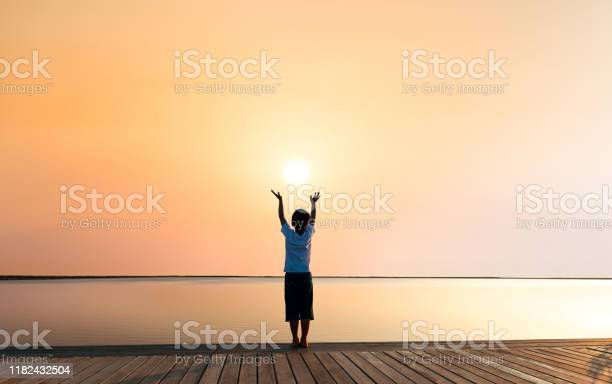 Photo of Little boy standing at sunset lakeside with arms outstretched