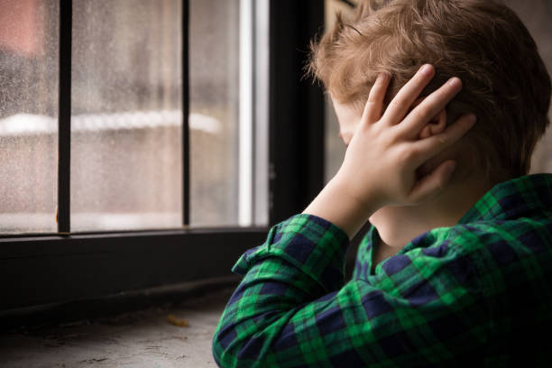 Little boy standing behind the window in sad mood. Sad Teenager looking in the Window and closing his ears with hands. Unhappy child in a plaid shirt. Alone at home. Upset. Little boy standing behind the window in sad mood. Sad Teenager looking in the Window and closing his ears with hands. Unhappy child in a plaid shirt. Alone at home. Upset. autism stock pictures, royalty-free photos & images