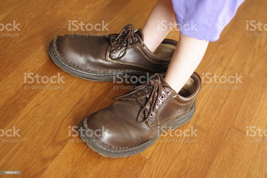 Little boy standing in dad's shoes stock photo