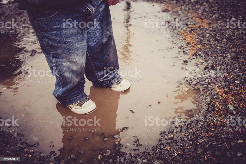 Little boy standing in mud puddle getting wet royalty-free stock photo