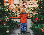 Little  Caucasian boy standing near Christmas tree in Rothenburg in winter