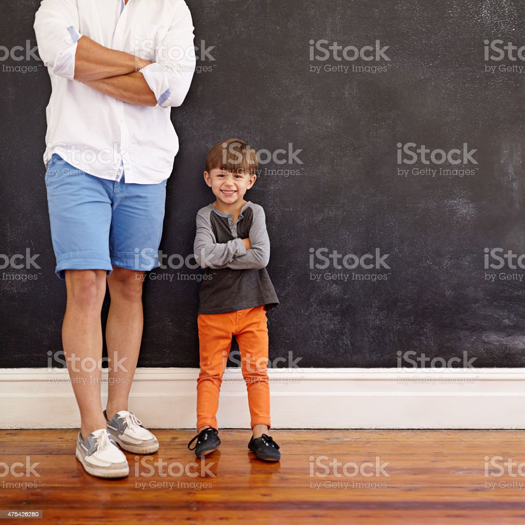 Little boy standing next to his father smiling stock photo