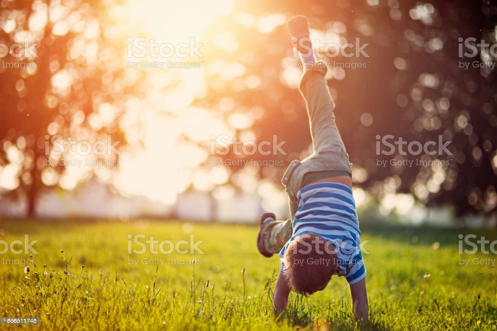 Little boy standing on hands on grass stock photo