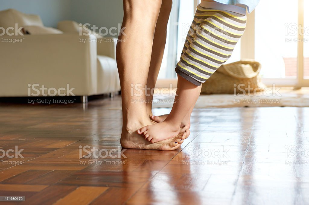 Little boy standing on mother's feet stock photo