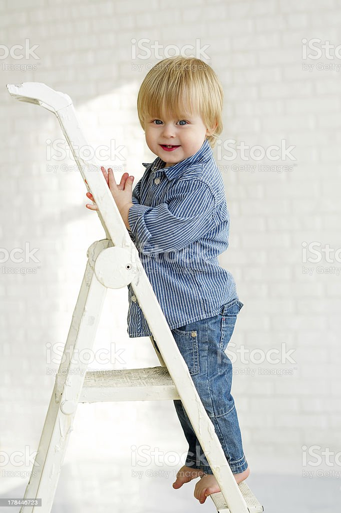 Little boy standing on the step of a metallic ladder royalty-free stock photo