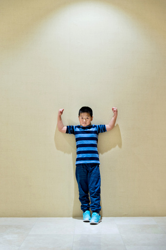 Little boy standing with arms raised