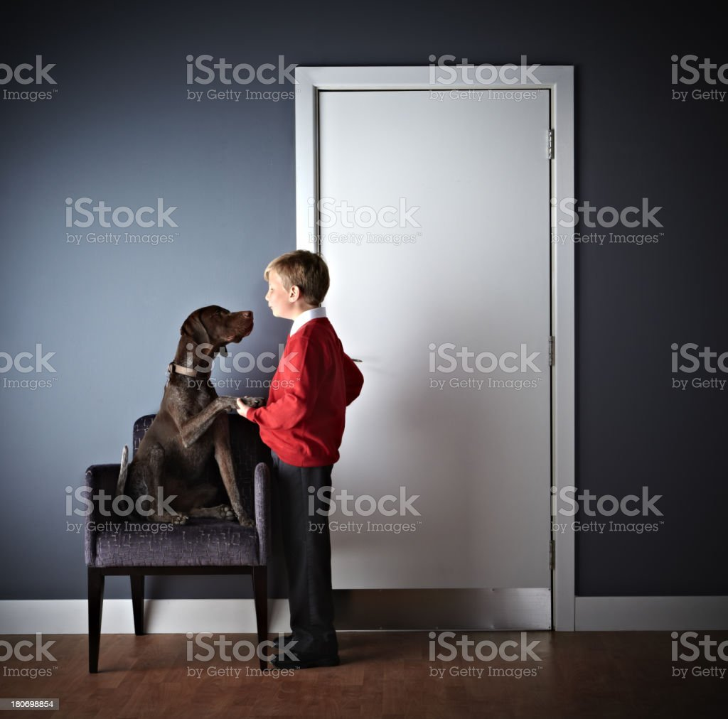 Little boy standing with dog outside vets door stock photo