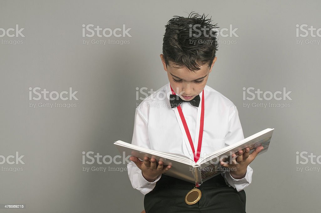 Little boy student reading book with medal royalty-free stock photo