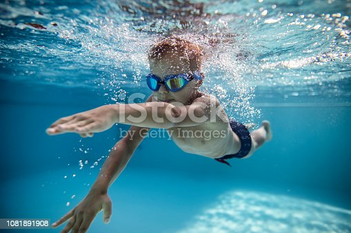 Portrait of little boy swimming underwater in the pool. Sunny summer day. Nikon D850