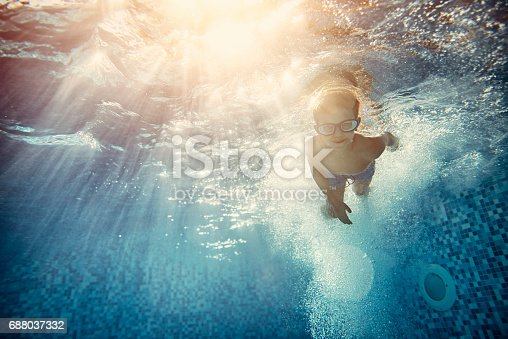 Happy little boy swimming underwater. The boy aged 6 have just jumped into the water. Sunny summer day.\n