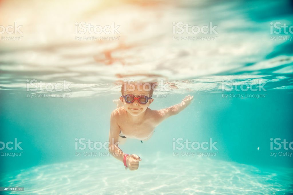 Little boy swimming underwater in pool stock photo