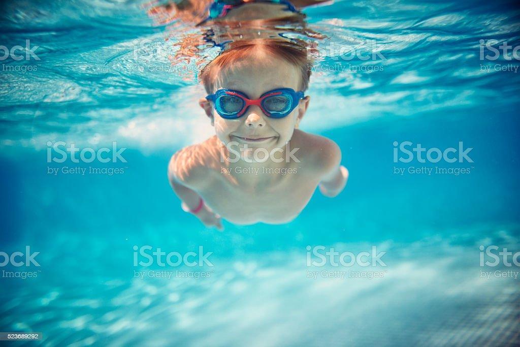 Portrait of smiling little boy enjoying underwater swim in the pool...
