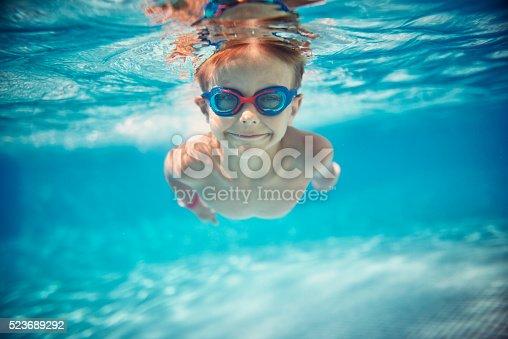 istock Little boy swimming underwater in pool 523689292