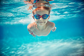 Portrait of smiling little boy enjoying underwater swim in the pool towards the camera. Sunny summer day.