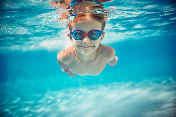 Little boy swimming underwater in pool Portrait of smiling little boy enjoying underwater swim in the pool towards the camera. Sunny summer day. swimming goggles stock pictures, royalty-free photos & images