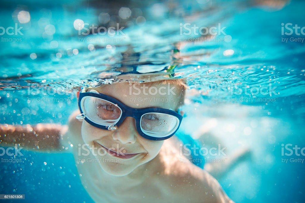 Petit garçon natation sous l'eau dans la piscine photo libre de droits