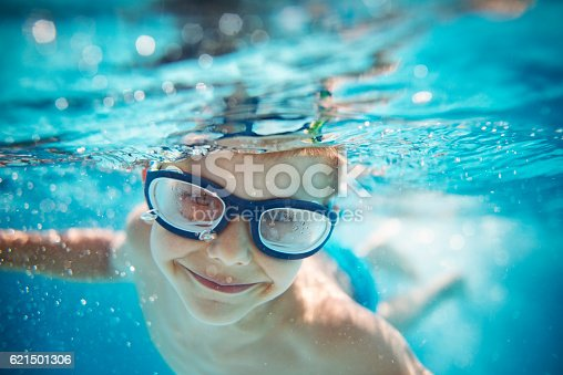 istock Little boy swimming underwater in pool 621501306