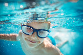 Portrait of smiling little boy enjoying underwater swim in the pool towards the camera. Sunny summer day. Copy space above the boy's head.