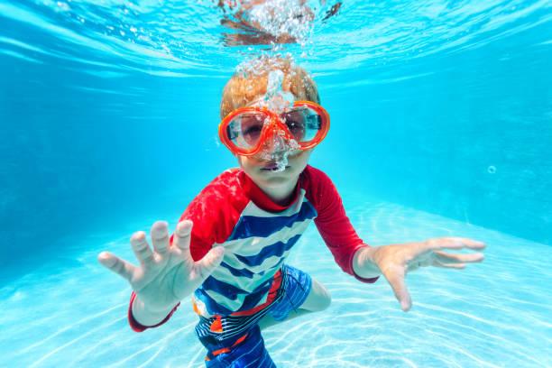 little boy swimming underwater stock photo