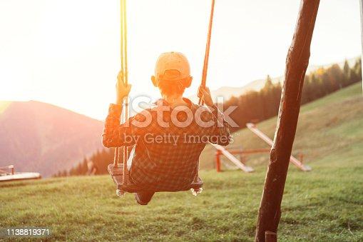 istock Little Boy swinging on the mountain kids park playground 1138819371