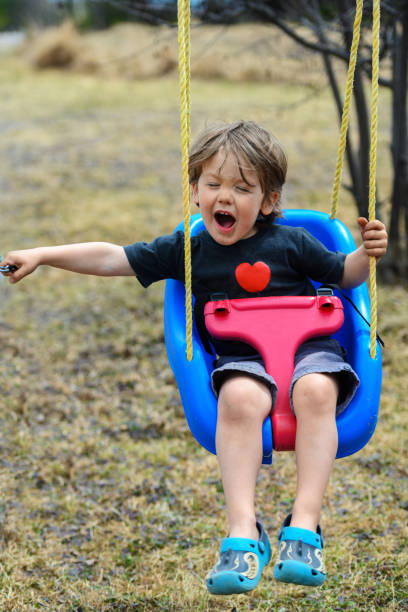 Little boy swinging stock photo