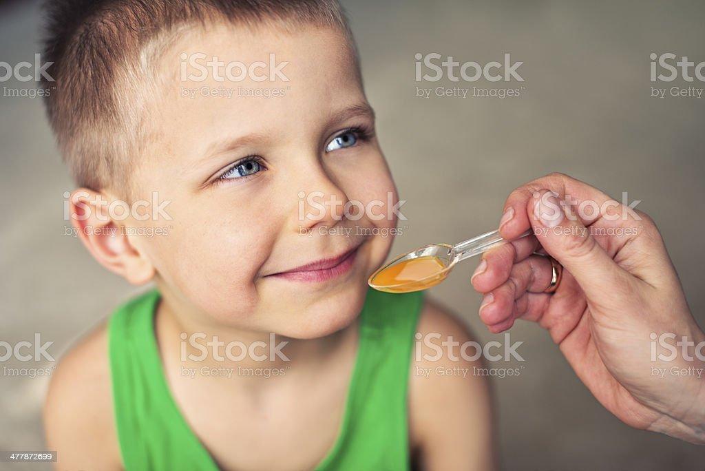 Little boy taking a medicine stock photo