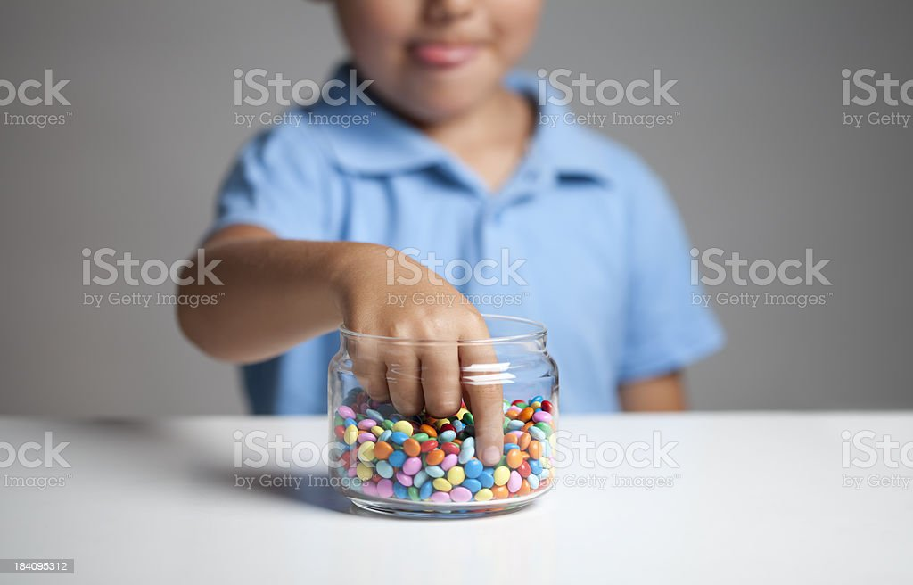 Little boy taking candy from jar royalty-free stock photo