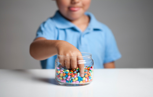 Little boy licking his lips while taking candy from the candy jar.